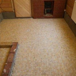 На полу в помывочной уложена мозаичная плитка