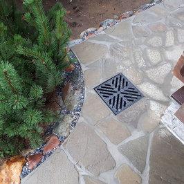 Из натурального камня выполнена отделка цоколя и выложена отмостка.