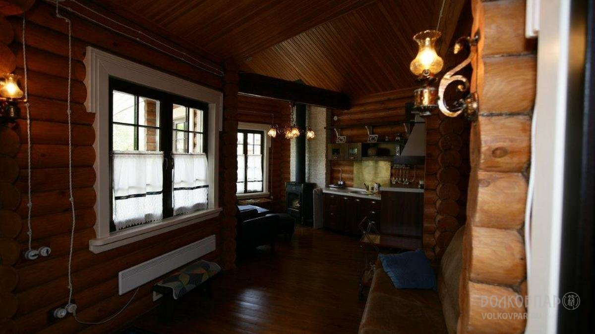 Расслабленное настроение в комнате отдыха создано за счет использования низкой кожаной мебели. Центром каминной зоны  стала элегантная французская чугунная печь. Созвучна общему настроению кованая люстра, оттеняющая золото деревянных стен