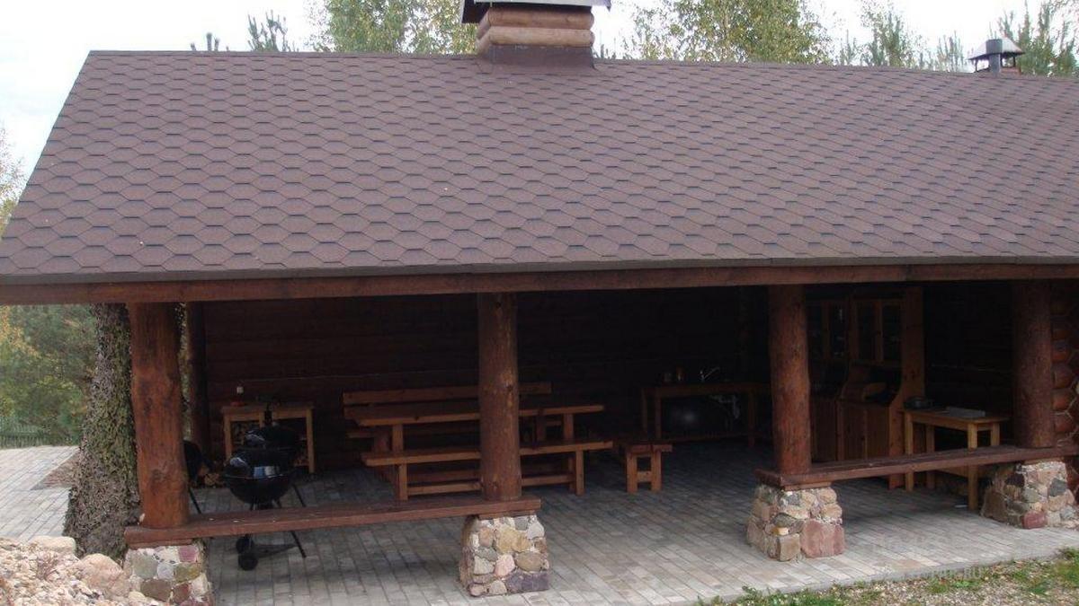 Площадка для барбекю площадью 67 кв. м. Длинные традиционные для русской  избы скамейки, а также деревянный стол из сосны становятся основной композицией