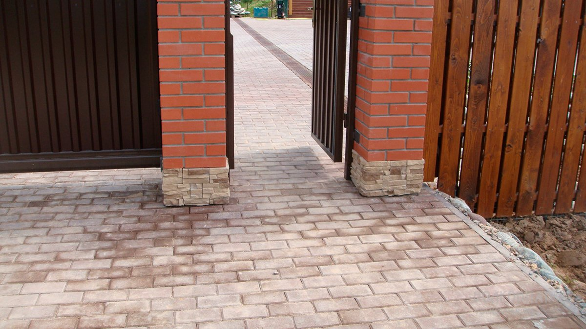 Столбы въездных ворот отделаны камнем