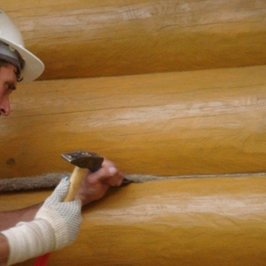 Выполняются работы по конопатке стен дома снаружи