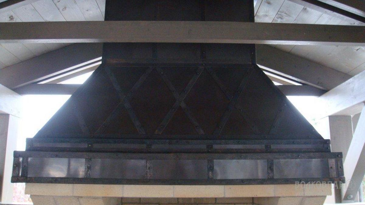 Дымосборник по всему периметру покрыт листовой медью и медными полосами, текстурированными «под старину»